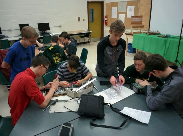 Students taking apart electronic appliances.