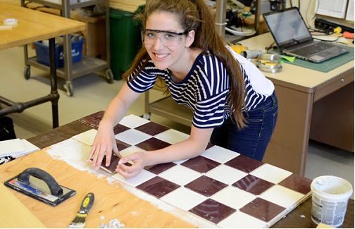 Student laying ceramic tiles in a checkerboard pattern.