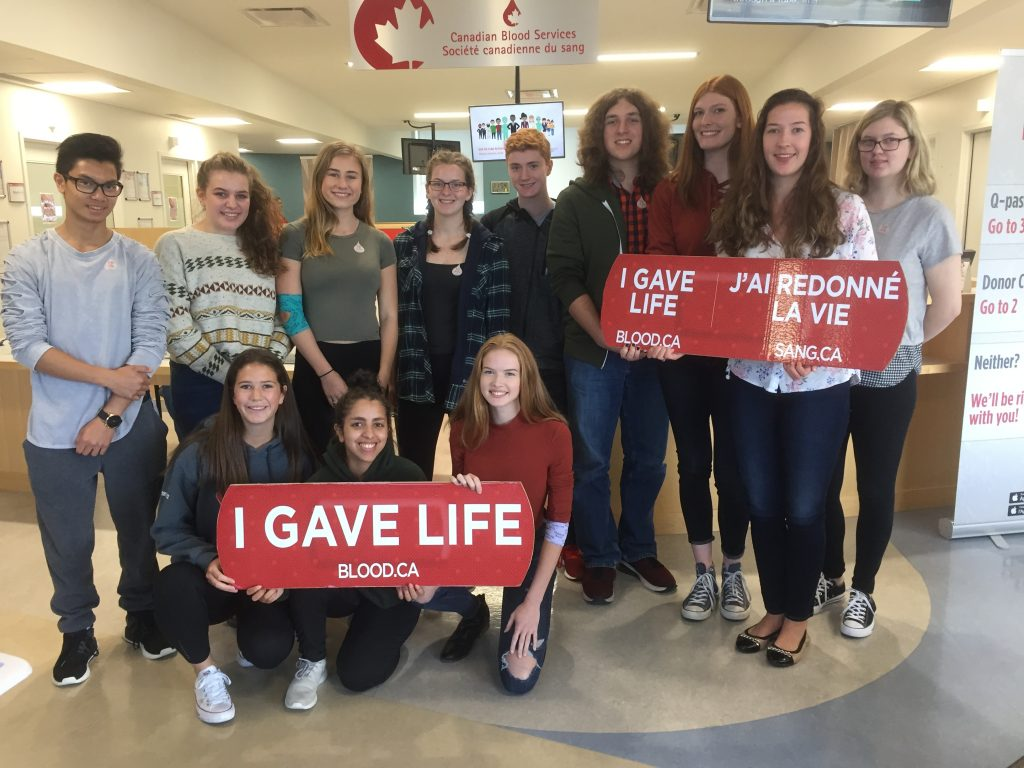 group of students at blood donor clinic holding signs that say