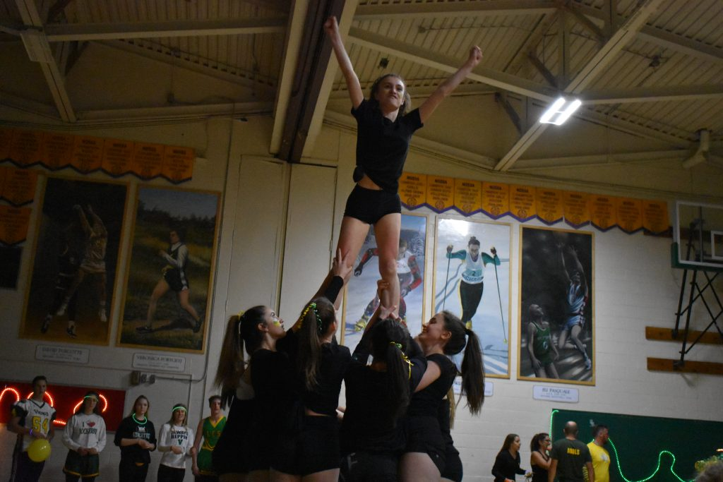 student being lifted at the end of cheerleading routine
