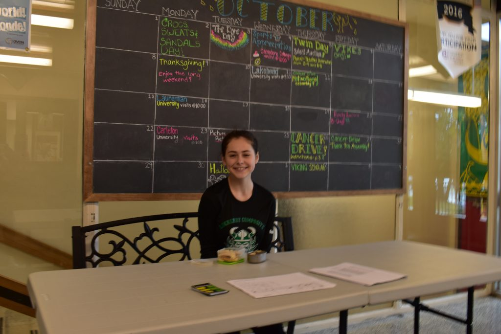 student sitting at a table in front of a chalkboard calender