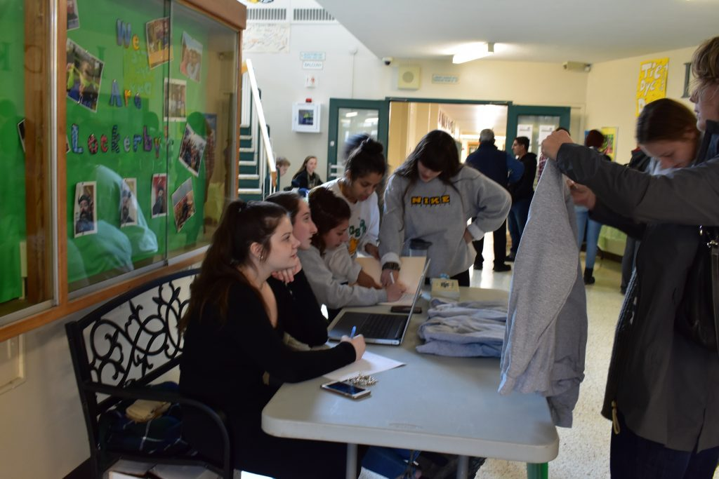students selling sweaters