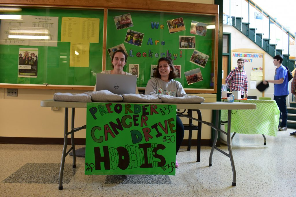 two students posing at the sweater selling table