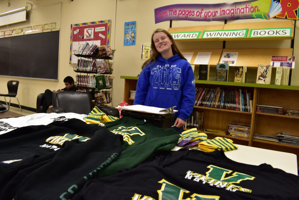 student posing behind a table selling lockerby apparel