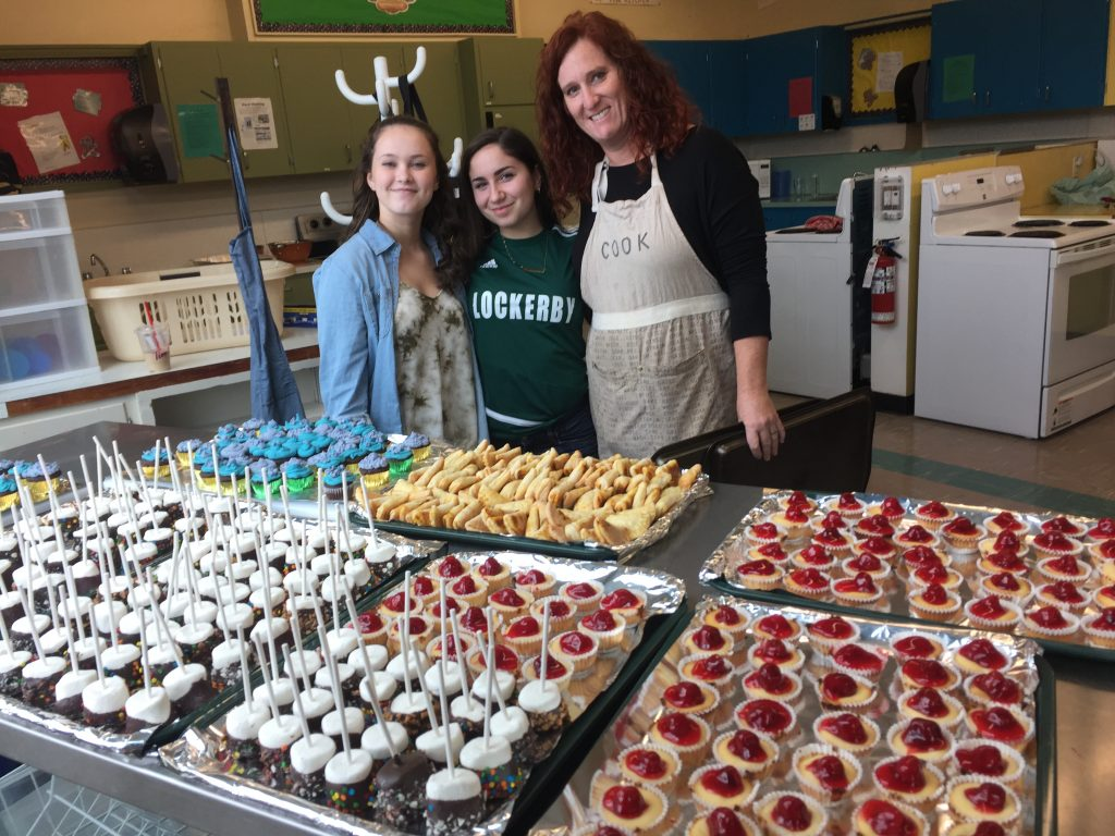 Teacher and students standing behind trays of food.