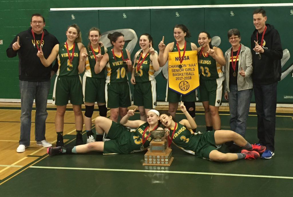 Girls' basketball team posing with trophy.
