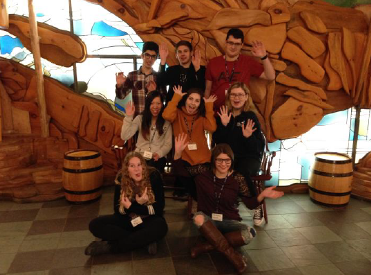Group of students posing in front of wood carvings.