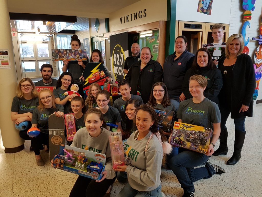 Students and staff in foyer displaying toys.