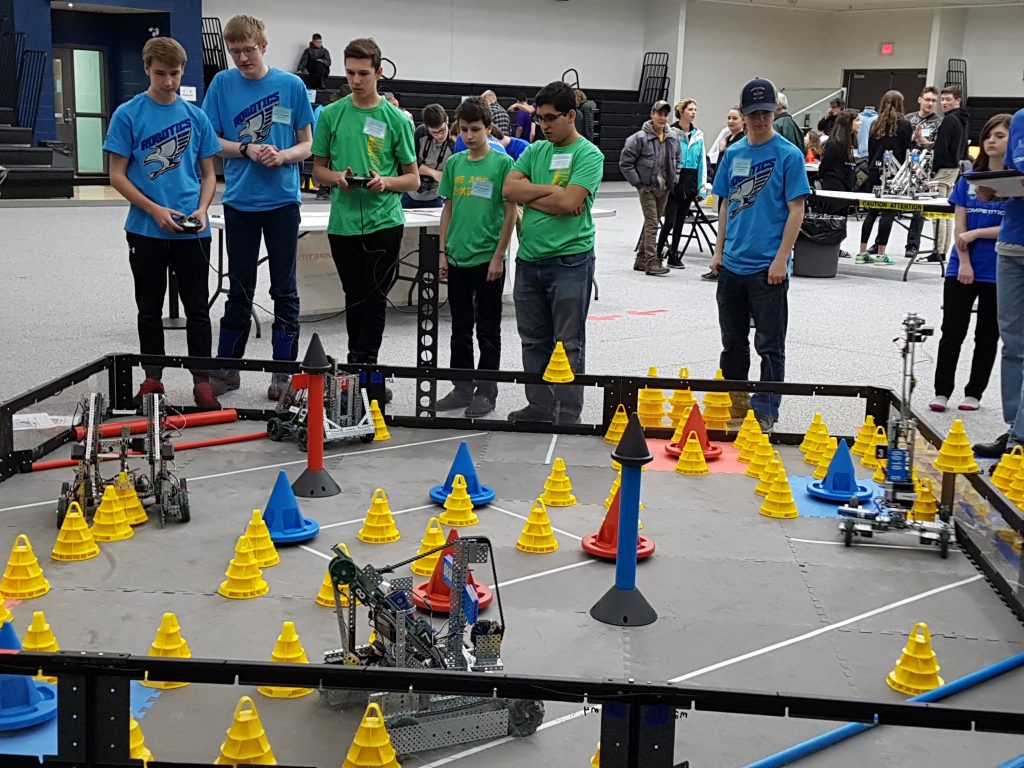 students standing around their robot, competing against another team