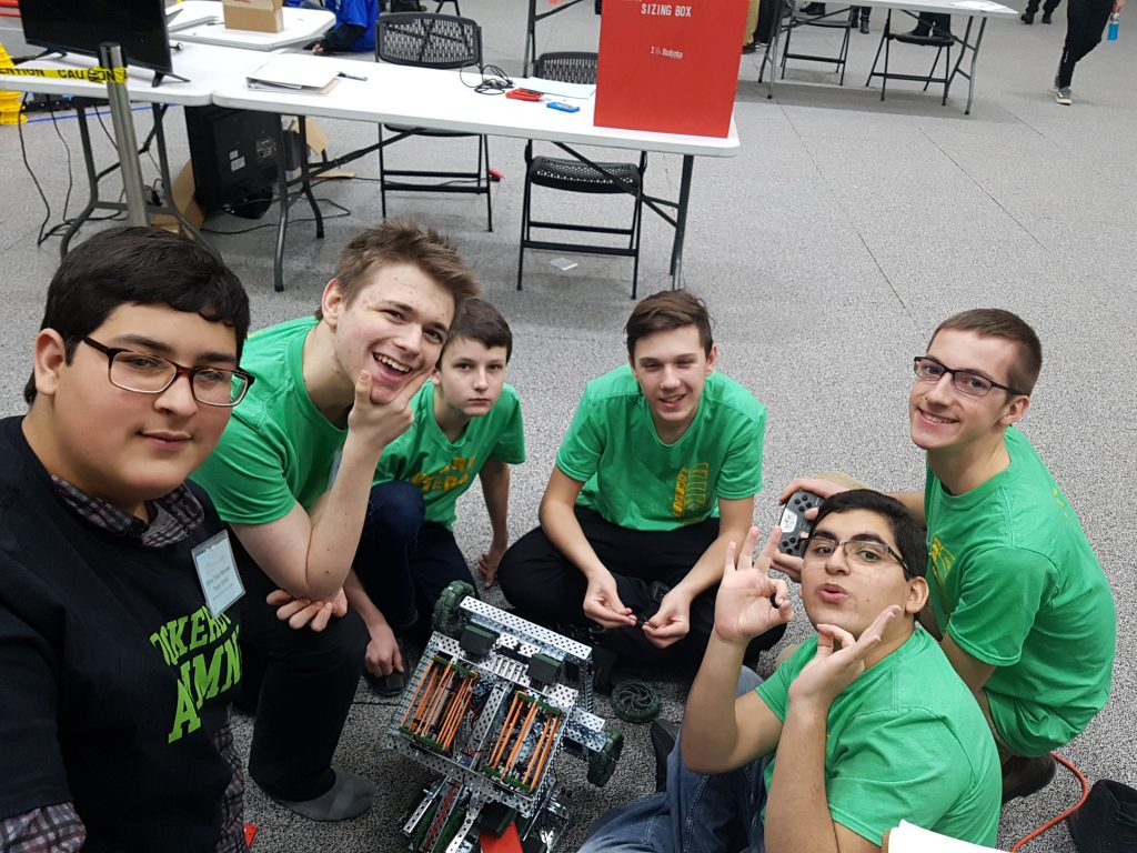 students posing for a picture with their robot