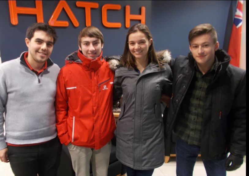 Four students in front of Hatch sign.