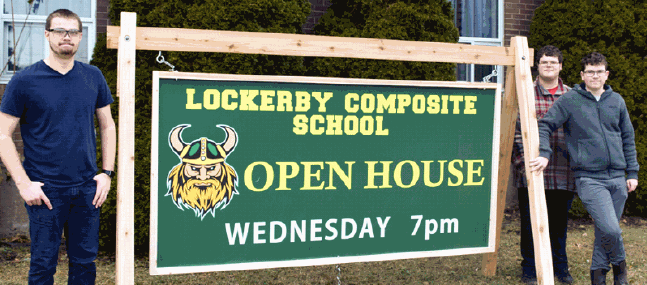 3 students standing with massive lawn sign about Lockerby open house.