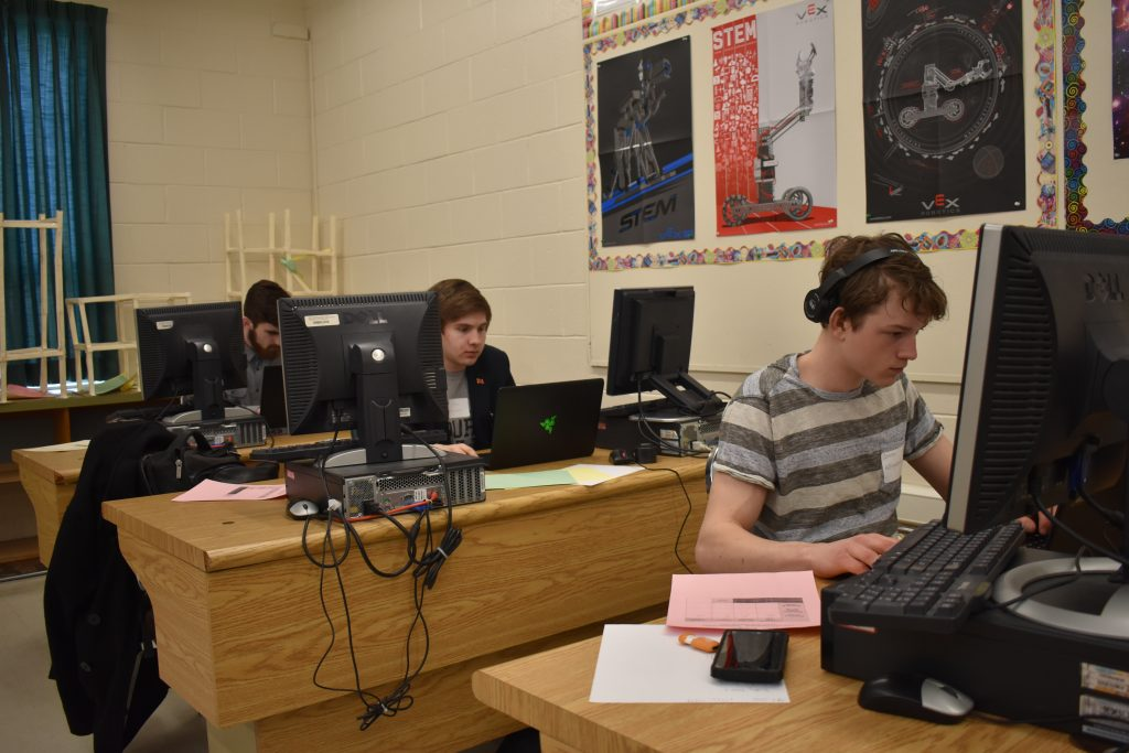 three students working on computers