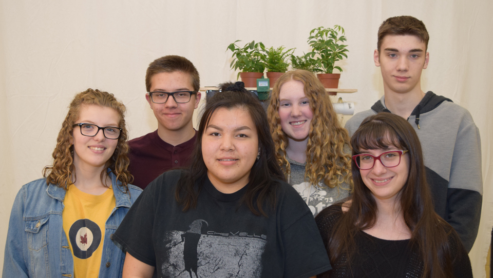 Students in a group in front of a plant shelf.