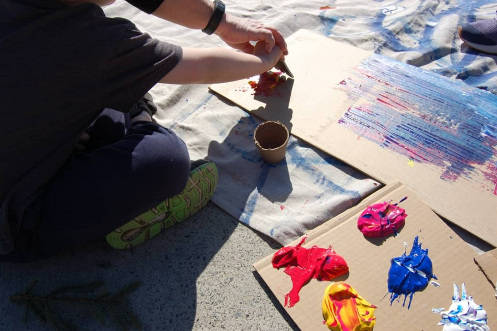 macleod student sitting on the ground using cardboard as a paint palette paints with the help of a lockerby student