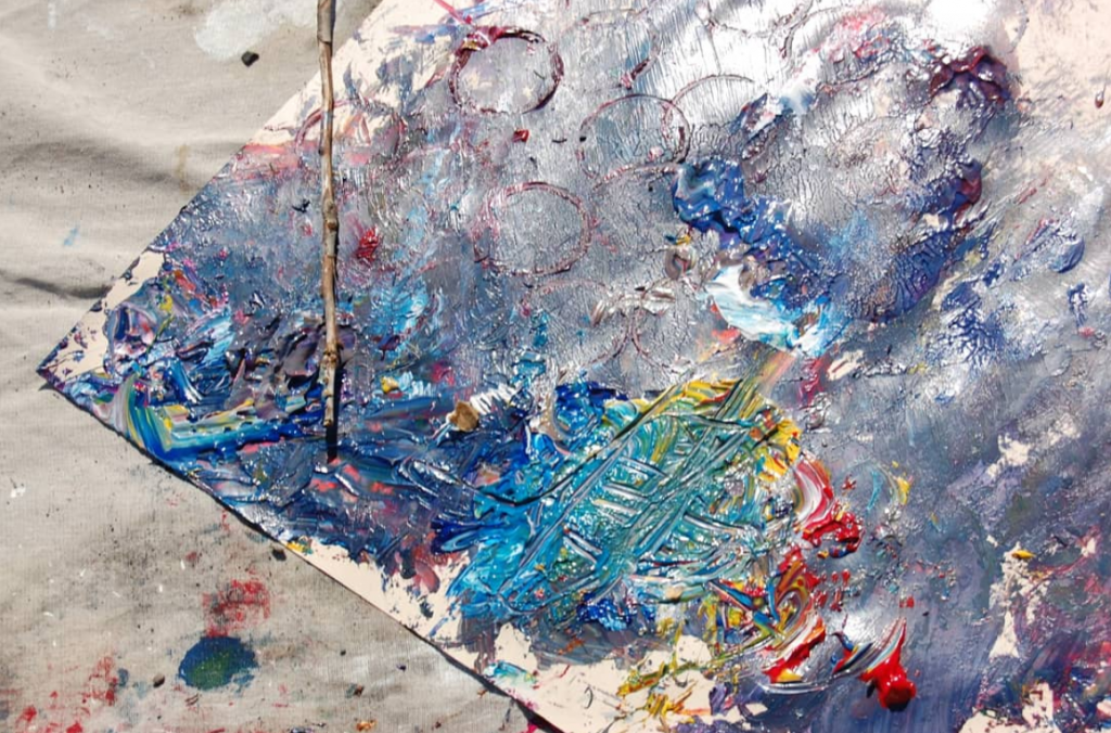 aftermath of a project; paints swirled together on a piece of cardboard
