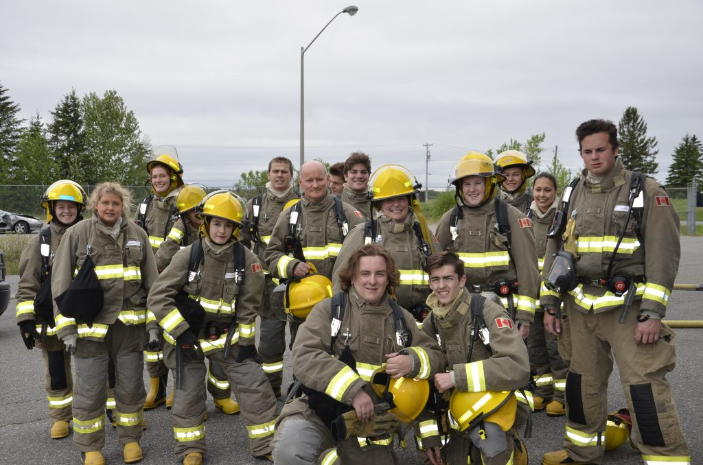 group of students in firefighter gear posing for the camera