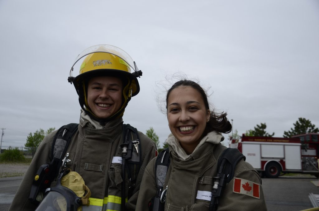 two students in bunker gear smile for the camera