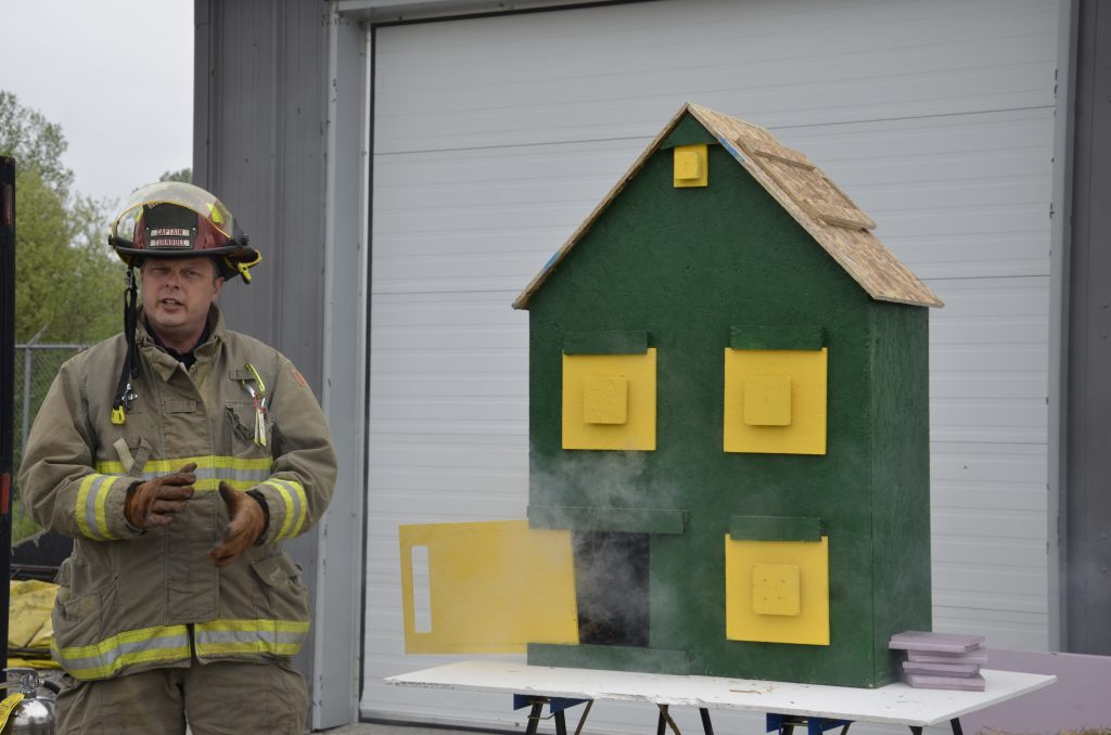 firefighter gives a demonstration with one of the model houses