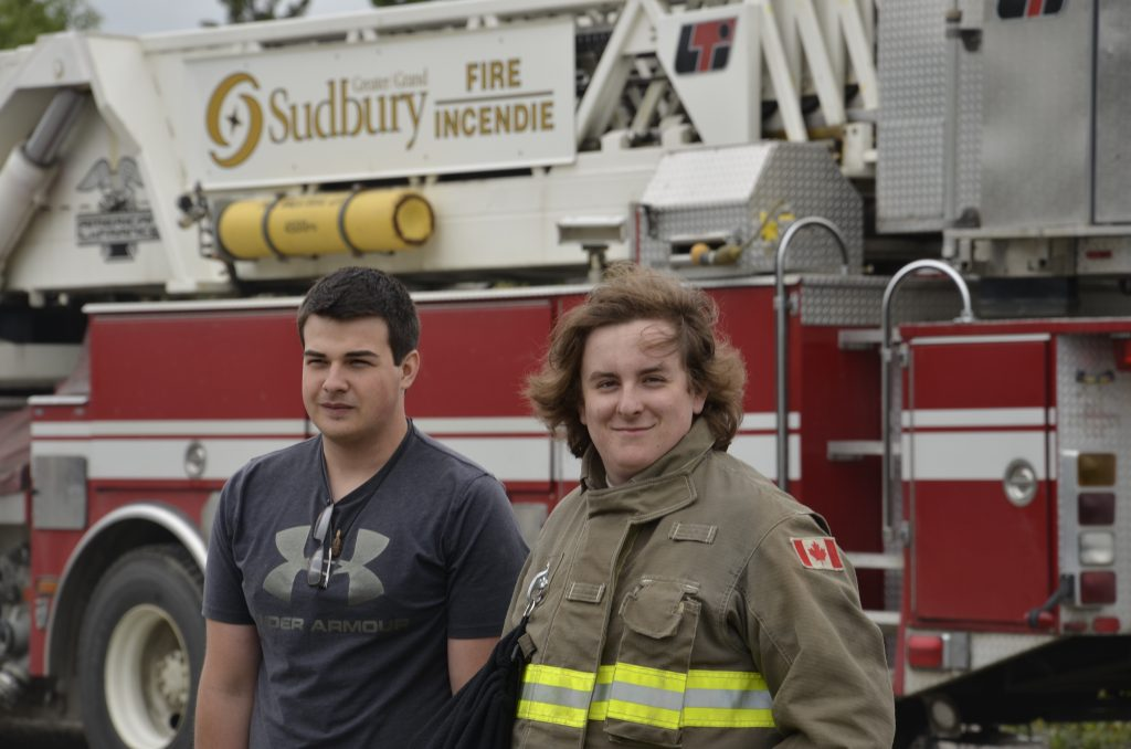 two students pose for a photo in front of a fire truck