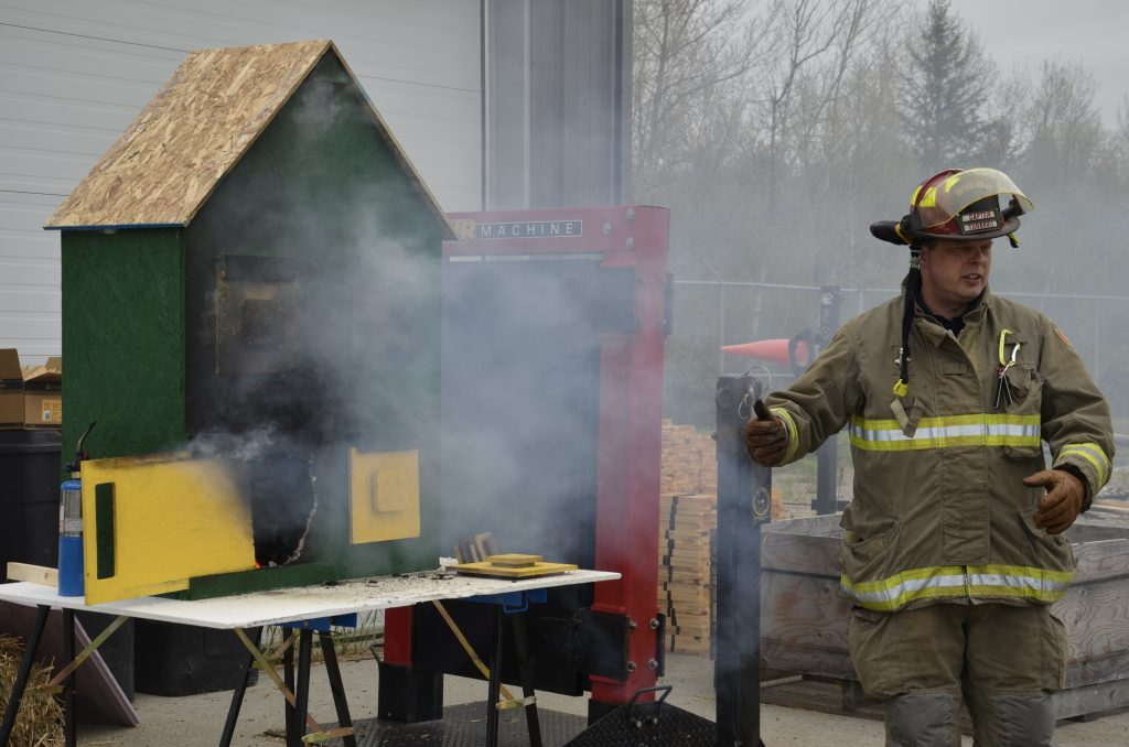 firefighter burns one of the model houses for a demonstration