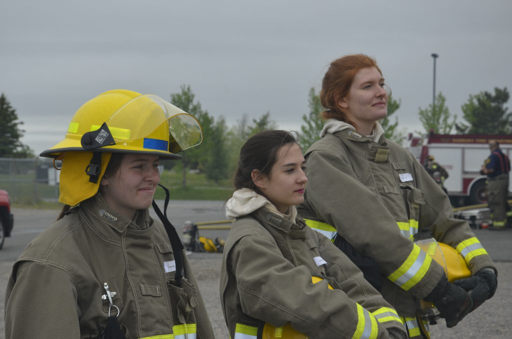 three students in bunker gear looking out of frame during a demonstration