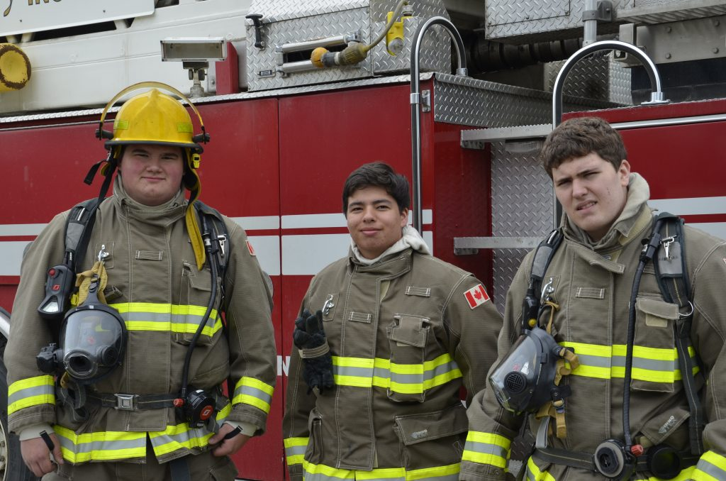 three students pose in from of a fire truck