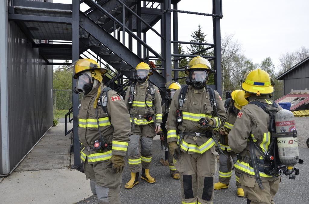 group of students in bunker gear and masks gathered in front of the training tower