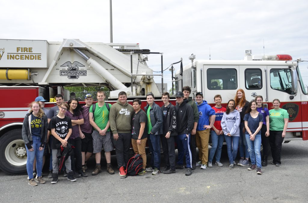 large group of students pose in front of a fire truck