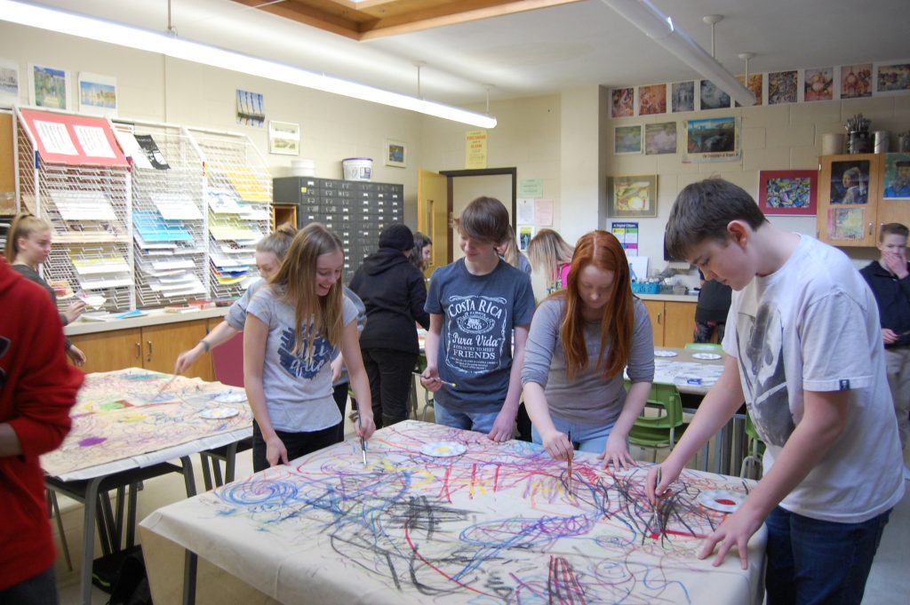 grade 9 lockerby students with a large piece of paper collaborating on a project