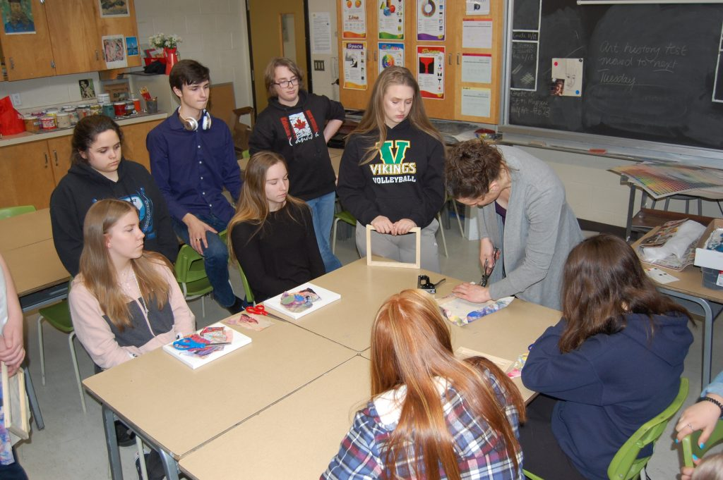 sarah king gold demonstrates how to stretch canvas as students watch