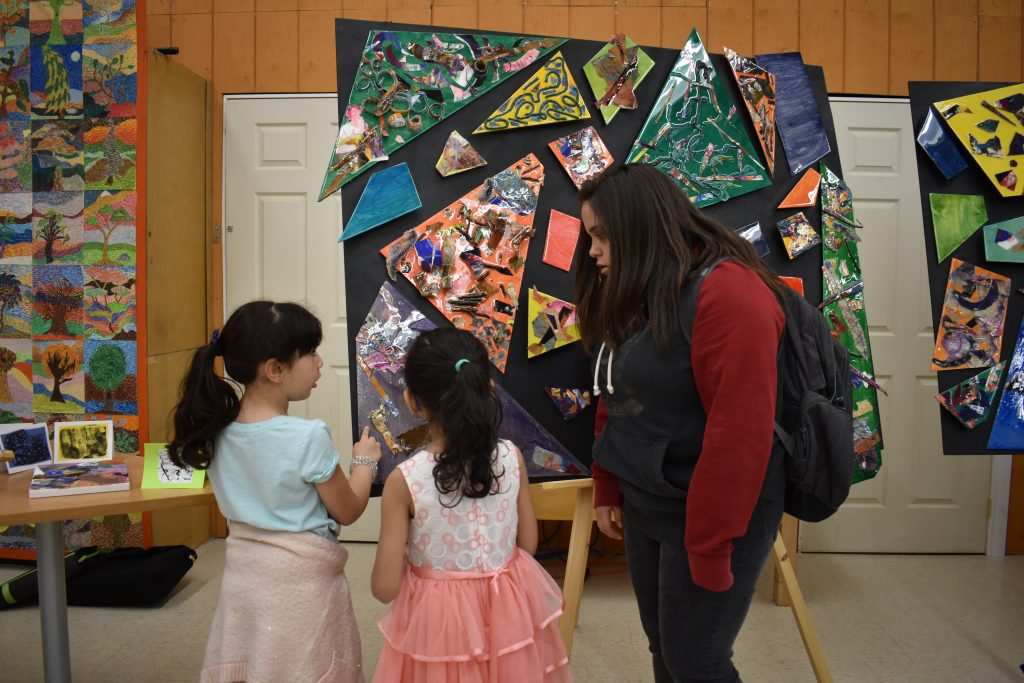 lockerby student and two macleod students examine an art piece together