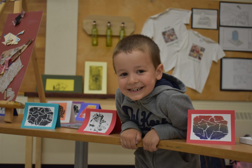 macleod student leaning on table and posing with art pieces