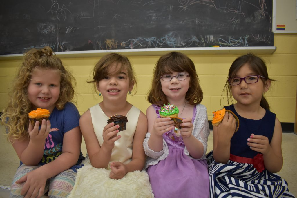 four macleod students eat cupcakes
