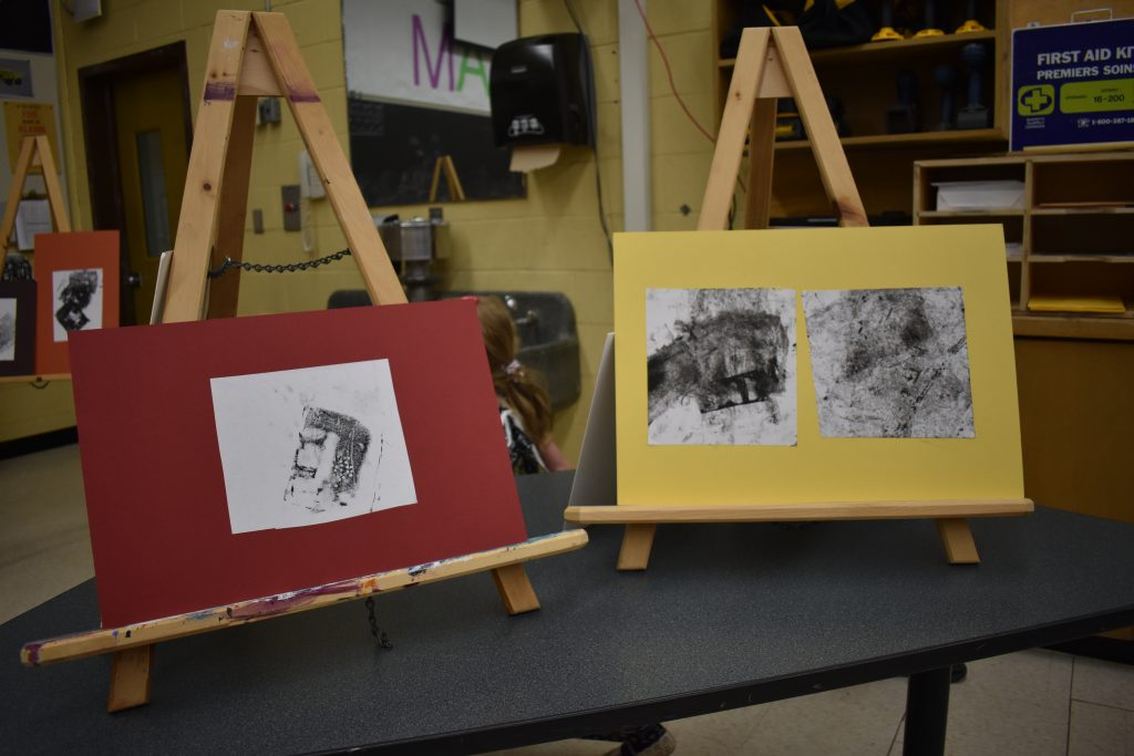 two easels on a table displaying two different art projects created by students