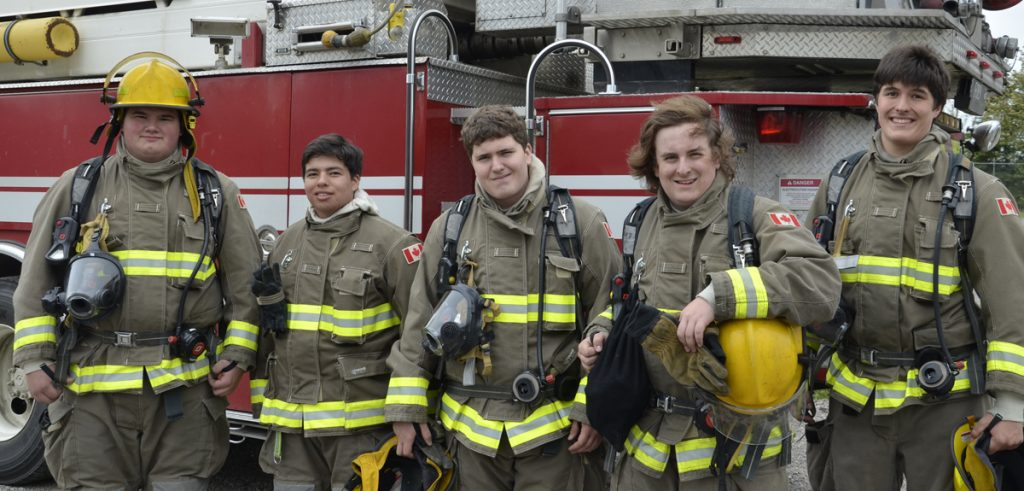 group of students pose in full gear in front of a fire truck