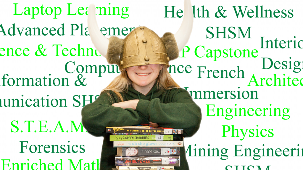 Student leaning on books wearing over sized Viking helmet.