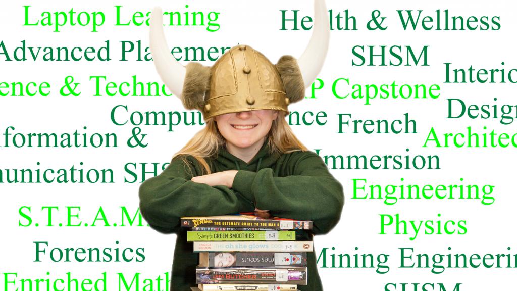 Student leaning on books wearing over sized Viking helmet.