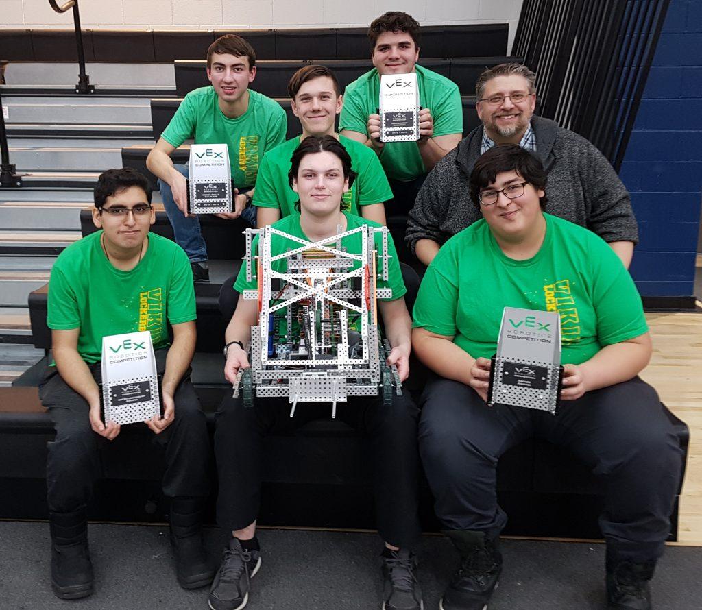 Robotics team holding trophies