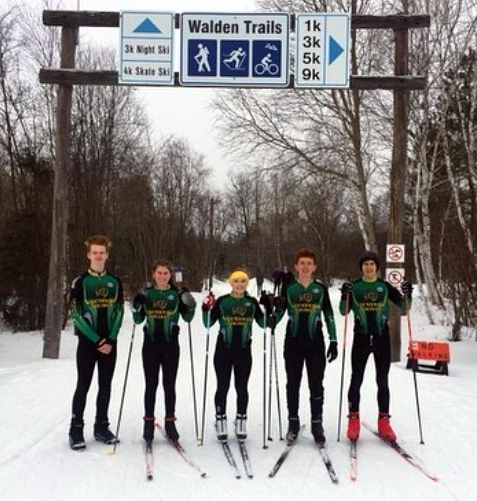 Cross country skiers under a sign